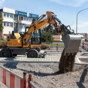 Excavadora sobre neumáticos A 910 Compact en el empleo intraurbano para la construcción de carreteras